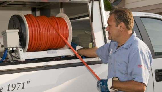 Technician Retrieving Hose from Truck